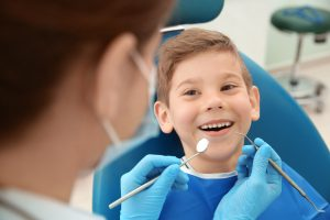 Dentist examining little boy's teeth in clinic