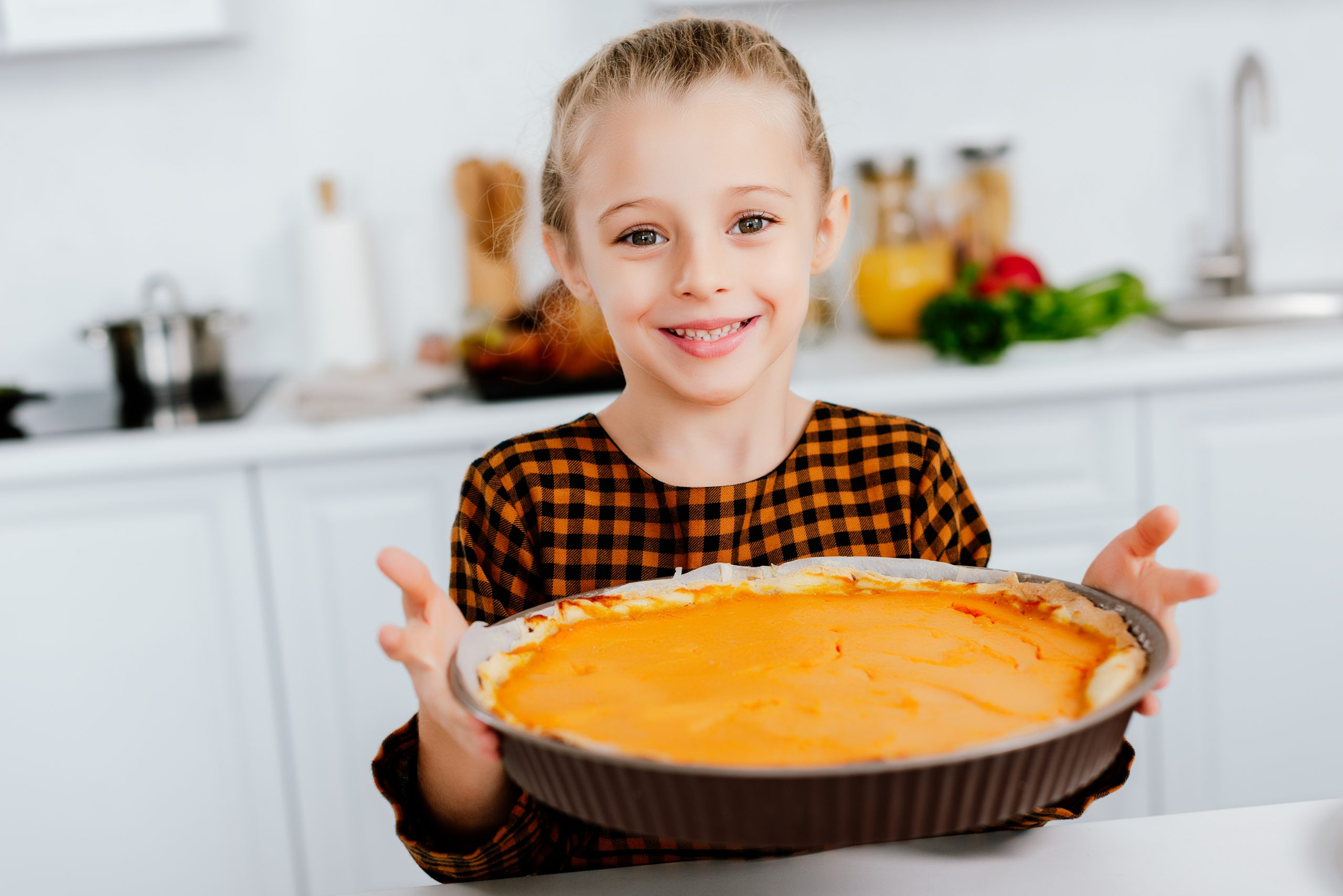 happy little child holding baking tray with thanksgiving pie