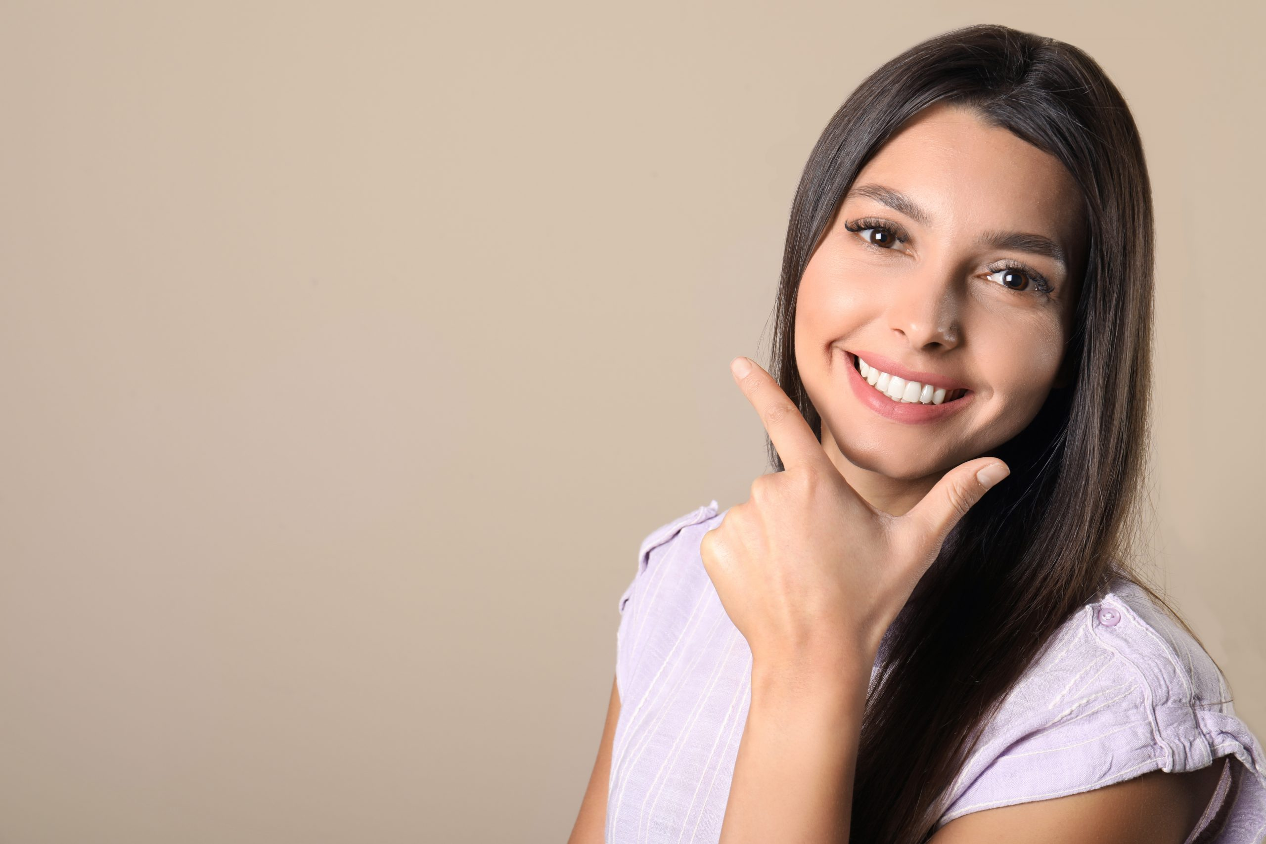 Young woman with healthy teeth on color background. Space for text