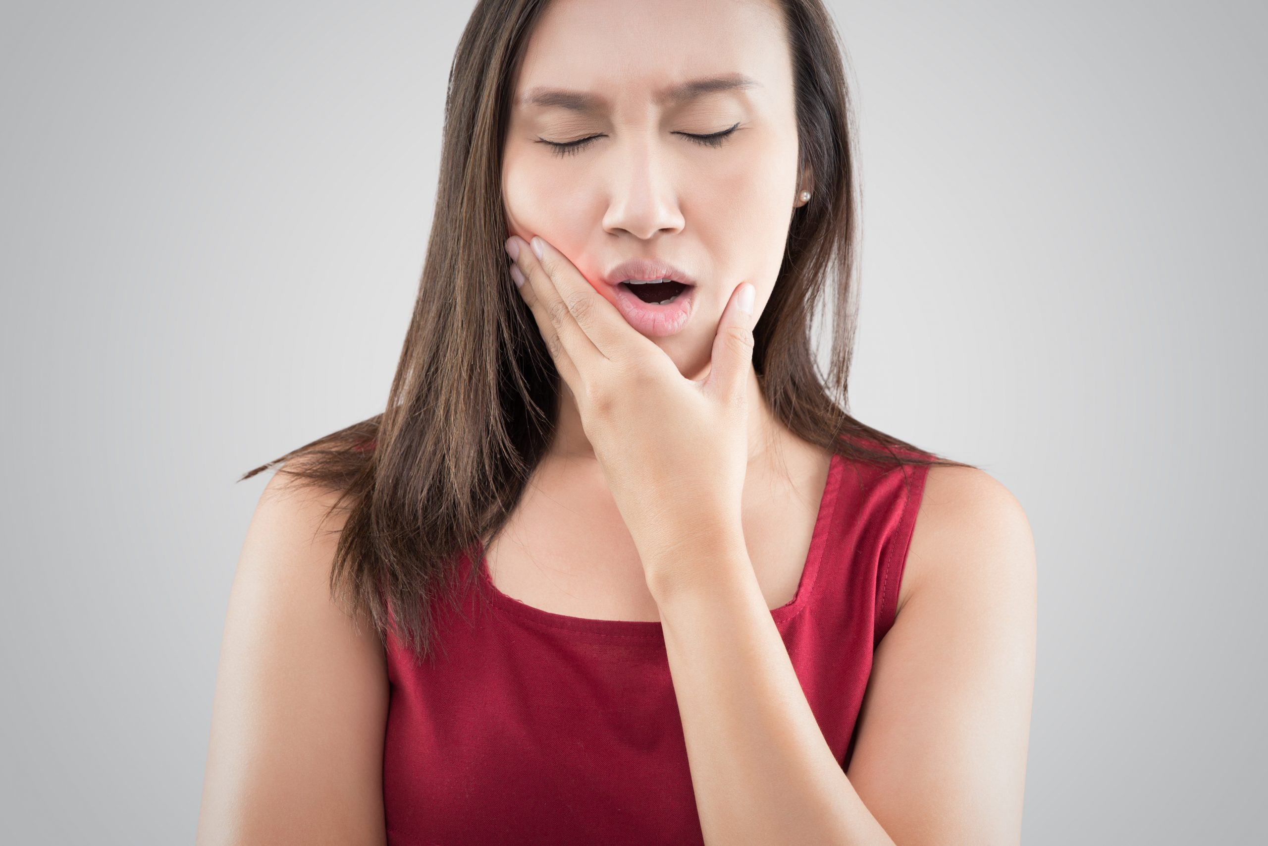 Suffering from a toothache. Beautiful young woman suffering from a toothache while standing against grey background
