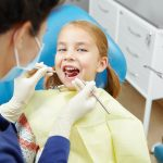 Female dentist examines of smiling child at the pediatric dentistry clinic. Happy little girl